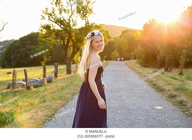 Woman on rural road wearing strapless dress looking over shoulder at camera smiling