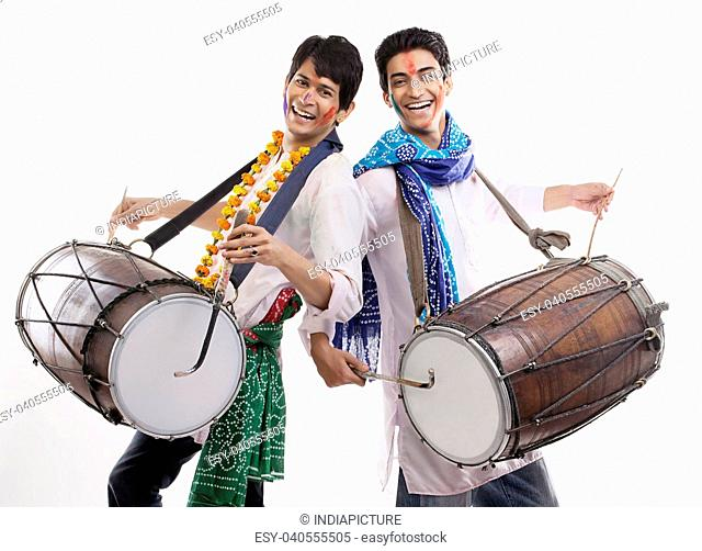 Two men playing on dholaks