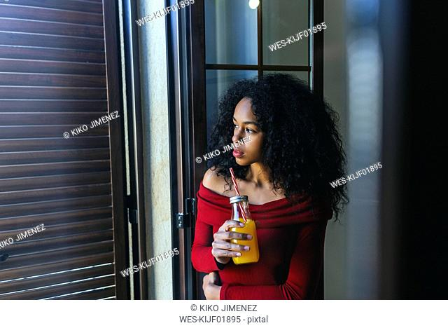 Young woman with beverage looking out of window
