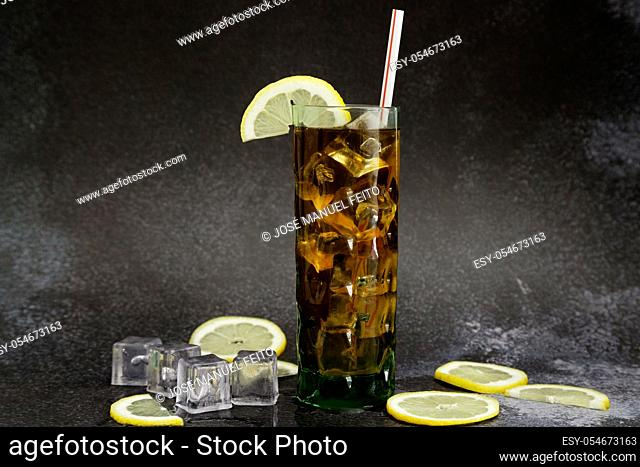 Iced tea glass with lemon slice and straw, lemon slices and ice cubes on dark background with copy space