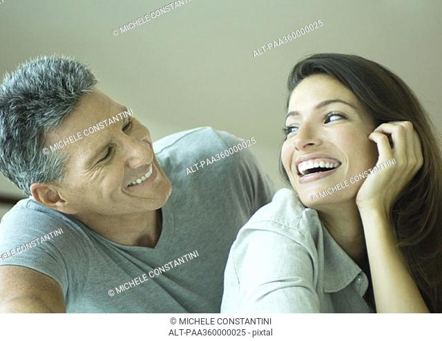 Couple smiling at each other, head and shoulders