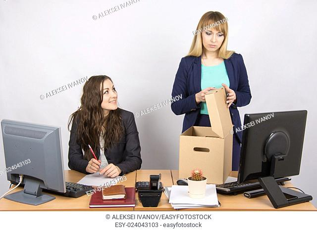 Office staff member with a smile, watching as a dismissed colleague collects things