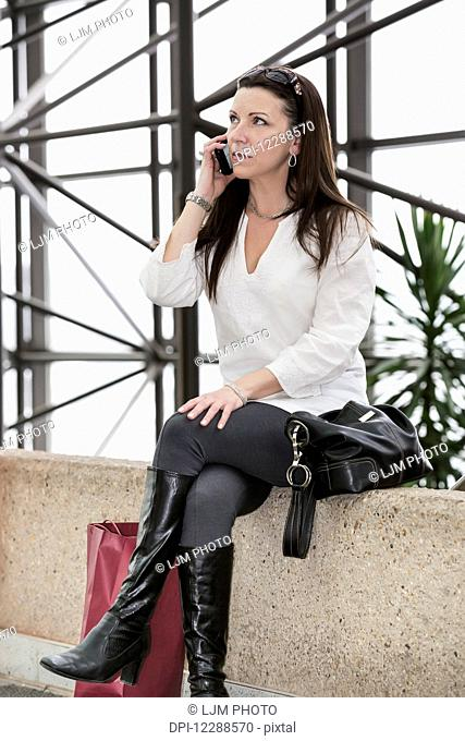 Business woman talking on her cell phone after taking a shopping break during her work day; Edmonton, Alberta, Canada