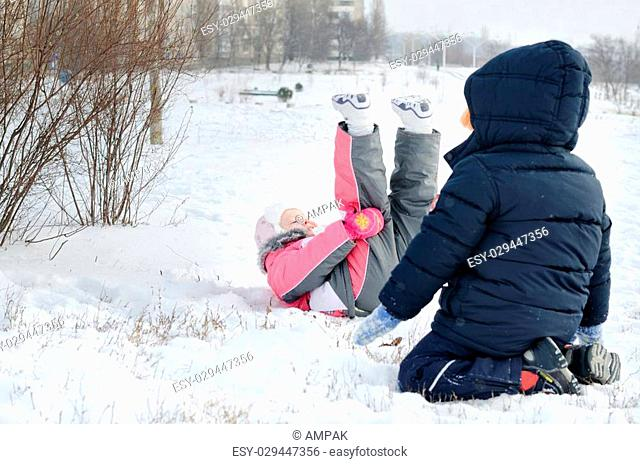 Two small children frolicking in the snow with a little girl lying on her back with her legs in the air in a fashionable pink winter outfit