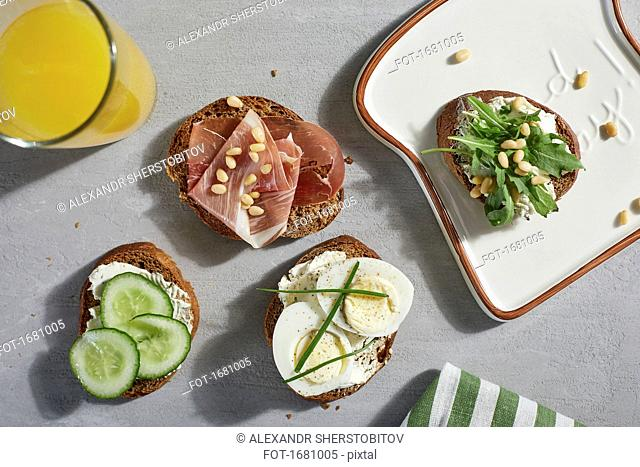 Directly above shot of open faced sandwiches with juice on table