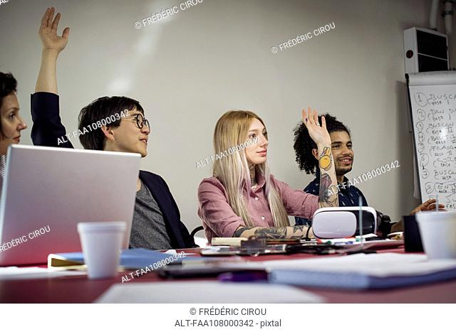 Office workers voting during business meeting