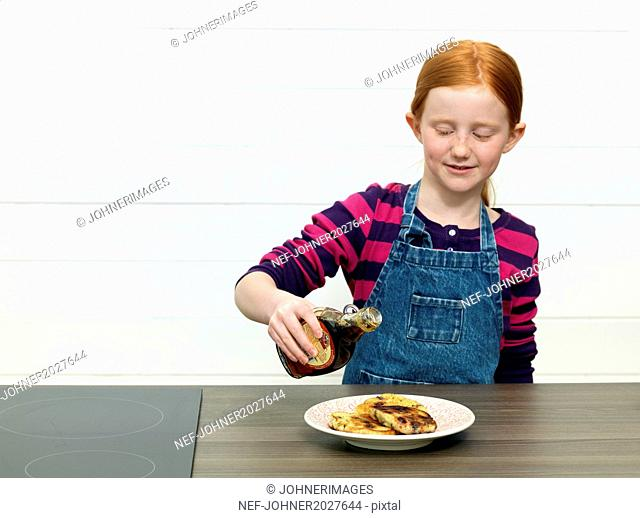 Girl pouring maple syrup on pancakes
