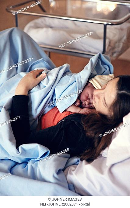 Mother sleeping with newborn baby on hospital bed
