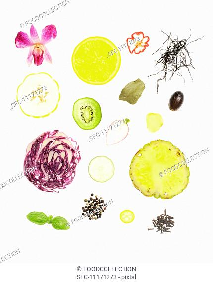 Assorted Slices of Vegetables, Fruit, Herbs and Seeds on a White Background