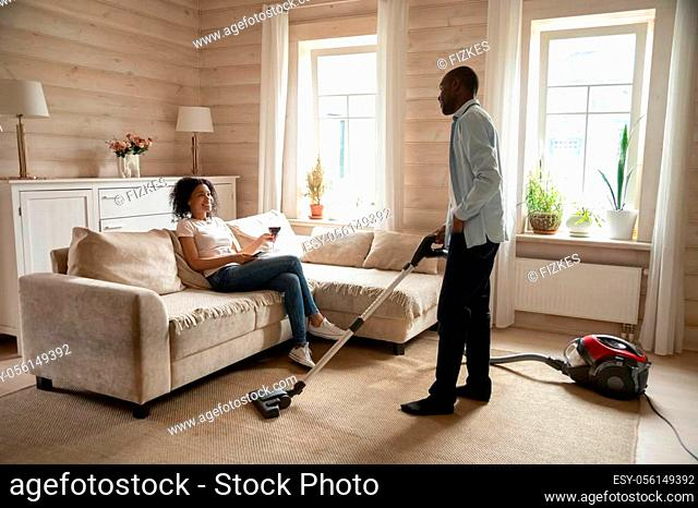 Young african American wife relax on couch in living room drinking wine, biracial husband clean house carpet with vacuum cleaner