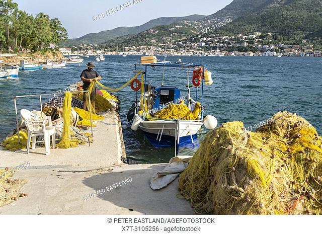Fisherman and fishing nets on the North harbour quay in Vathy harbour with the town of Vathy in the background. On the island of Ithaca, Ionian Sea, Greece