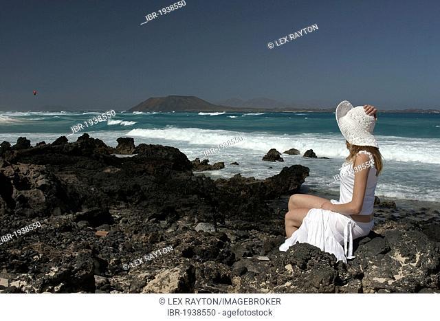 Woman on a rocky beach, Corralejo, Fuerteventura, Lanzarote in the back, Canary Islands, Spain, Europe