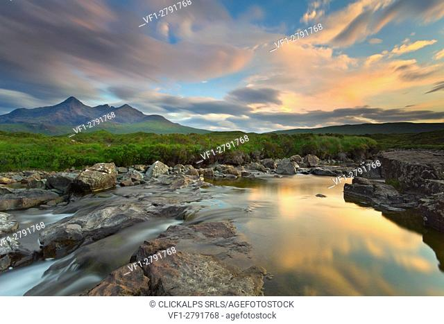 Isle of Skye, Scotland, Europe. The last sunset colors reflected in the water. In the background the peaks of the Black Cuillin