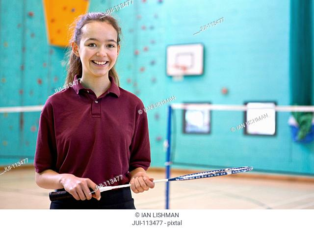 Portrait smiling high school student holding badminton racket in school gymnasium