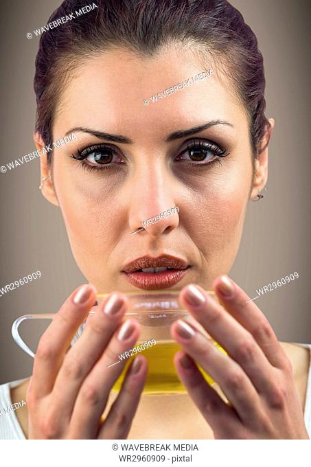 Close up of woman drinking tea against brown background