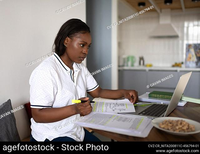 Black student with papers using laptop