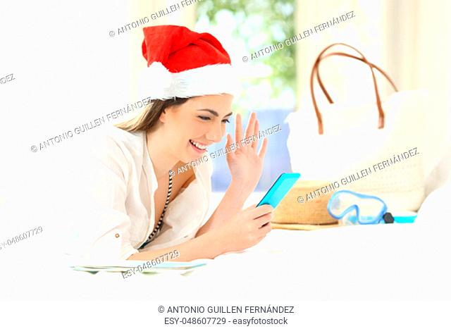 Happy woman on christmas holidays talking in a video call with a smart phone