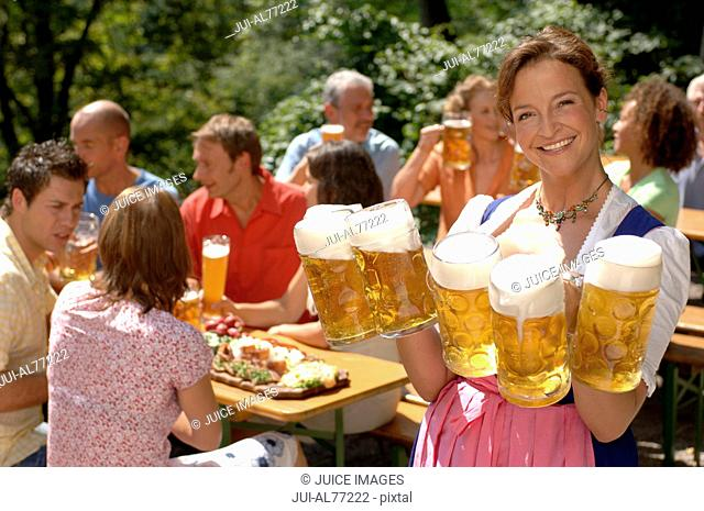 View of a young woman serving beer, beergarden, Munich, Bavaria, Germany