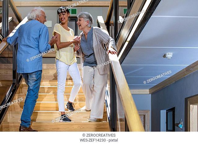 Nurse helping laughing seniors on staircase