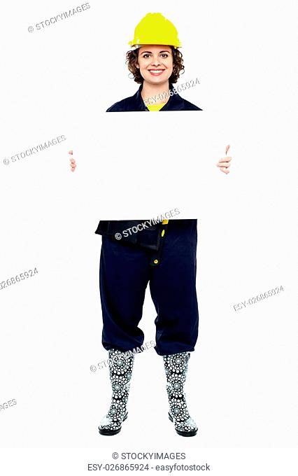 405ab4e7f82 Full length portrait of a woman in jumpsuit presenting blank ad board