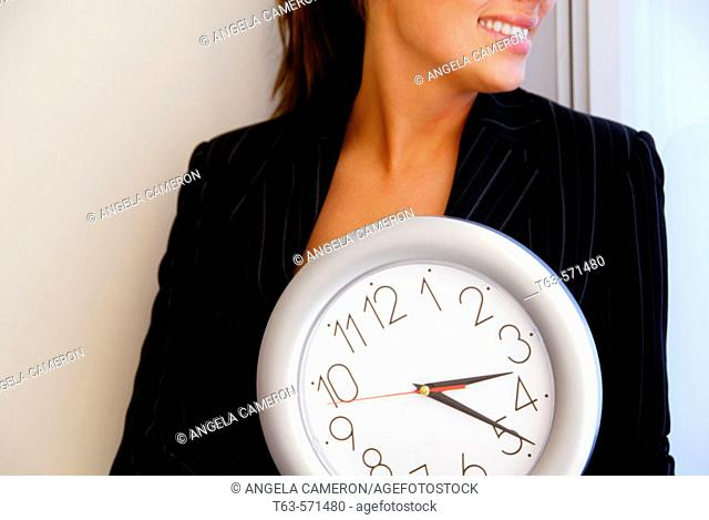 20 yr old young woman holding clock in office
