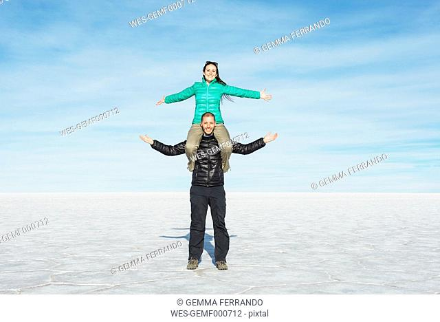 Bolivia, Salar de Uyuni, couple, woman sitting on shoulders of man