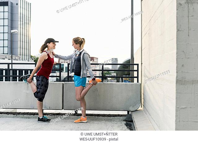 Two active women stretching in the city