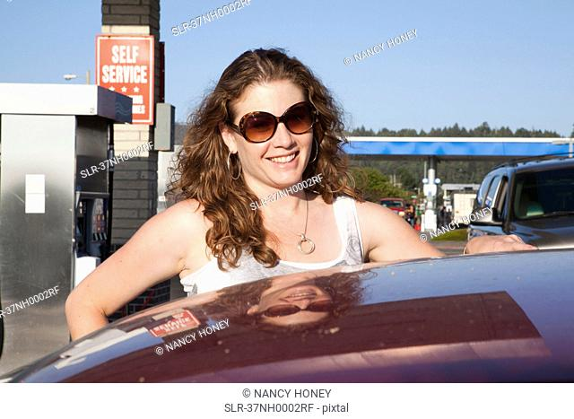 Smiling woman pumping gas at station