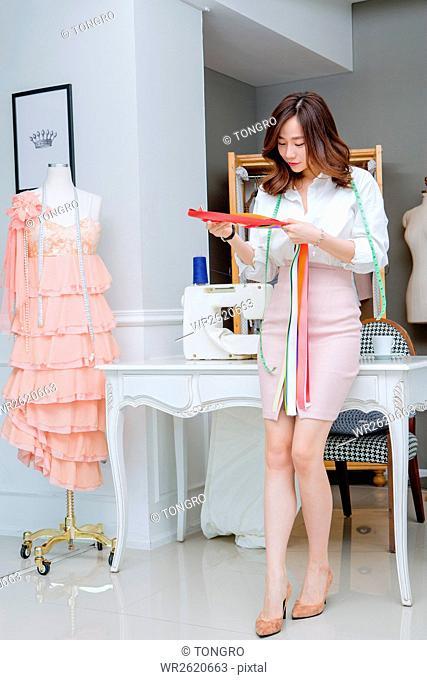 Female fashion designer working ribbons