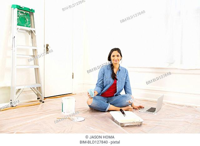 Mixed race woman relaxing while painting room