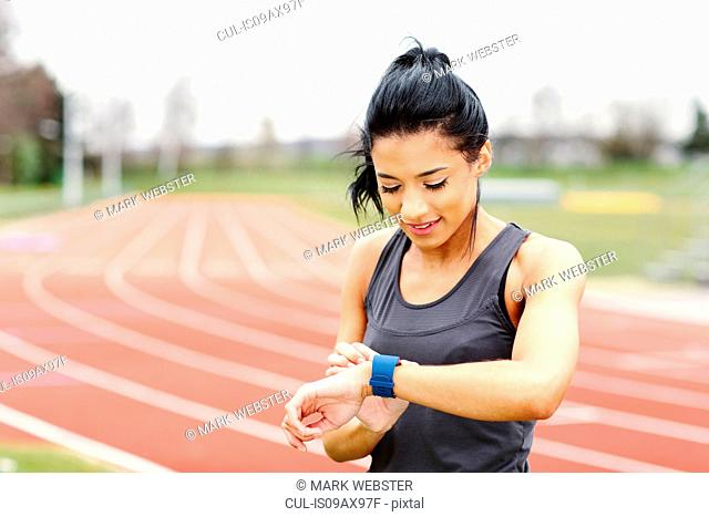 Young woman on running track, checking watch