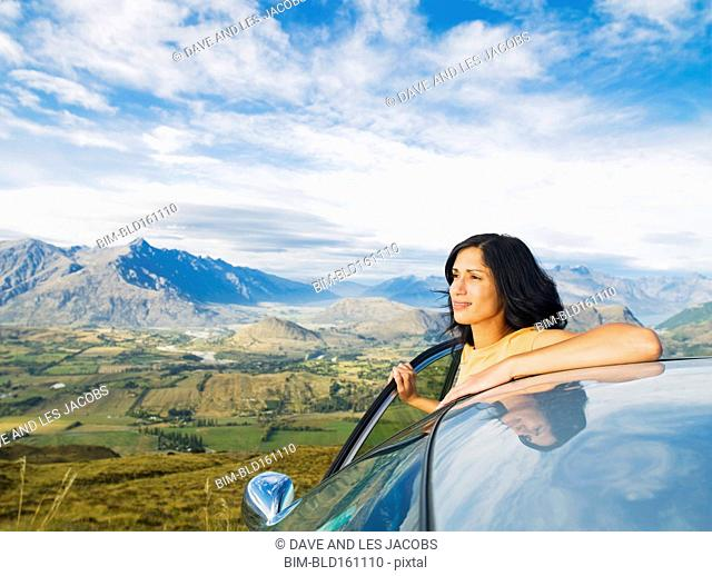 Hispanic woman admiring view from remote hilltop, Queenstown, South Island, New Zealand