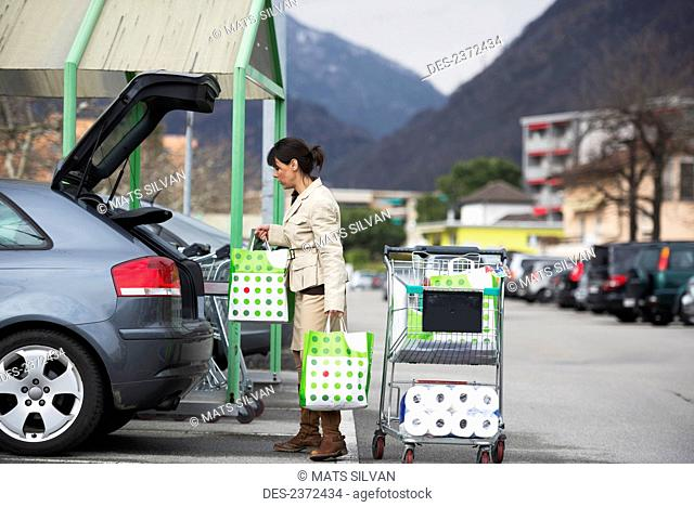 A Woman Loads Her Car With Shopping Bags In A Parking Lot; Ascona, Ticino, Switzerland