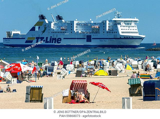 Tourists and daytime visitors use the summerly weather to sunbathe while in the background the ferry 'PeterPan' runs into the port