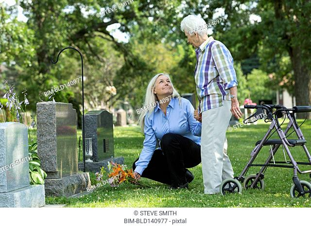 Caucasian mother and daughter visiting grave in cemetery