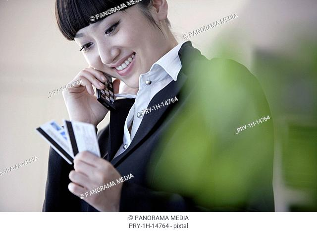 Close-up of a young woman using mobile phone and looking at credit cards