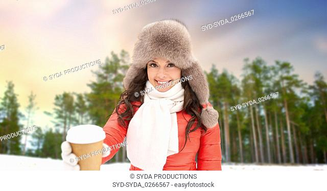 woman in fur hat with coffee over winter forest