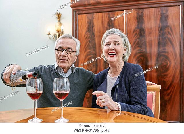 Happy senior couple drinking red wine