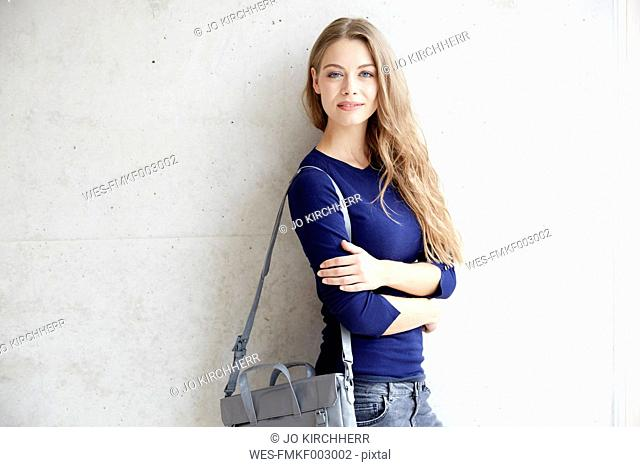 Smiling young woman at concrete wall