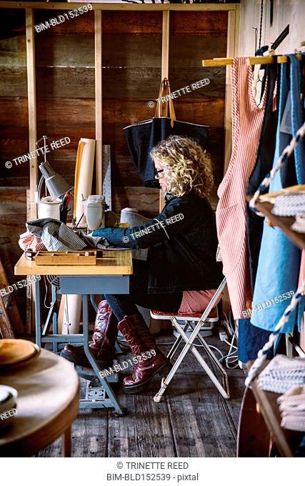 Caucasian seamstress working at desk