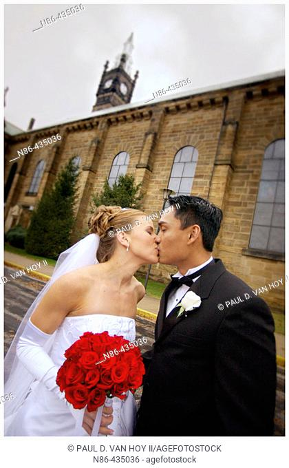 Young married couple kissing outside of church