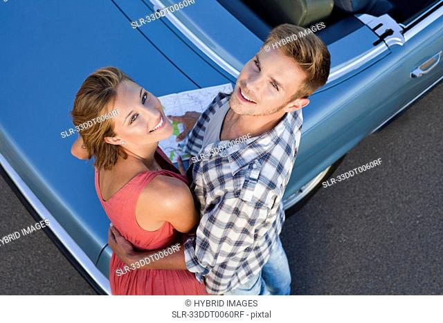 Couple hugging by convertible