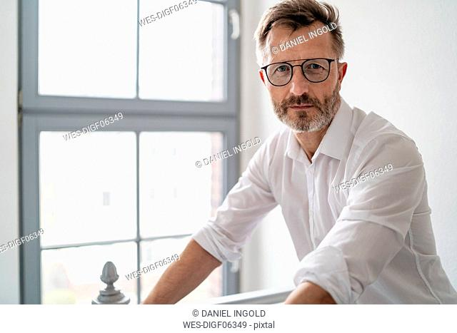 Portrait of confident businessman at the window in office