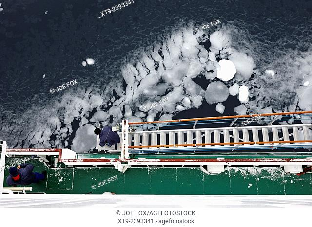 crew members set up gangway on expedition ship with frozen sea ice Anvers Island Antarctica