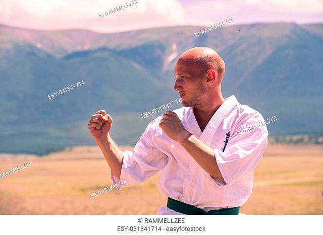 man in combat karate rack in the mountains