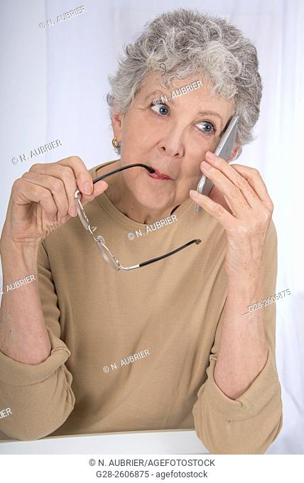 Thoughtful senior woman with grey hair, biting her glasses and using a mobile phone