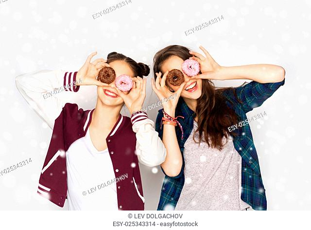 winter, christmas, people, holidays and fast food concept - happy smiling pretty teenage girls or friends with donuts making faces and having fun over gray...