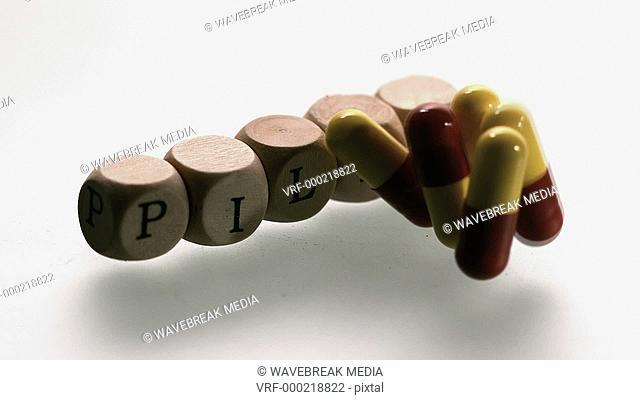 Medicine capsules falling in front of dice spelling pills