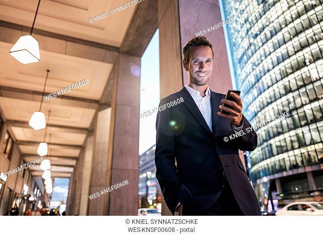 Germany, Berlin, portrait of smiling businessman at Potsdamer Platz in the evening