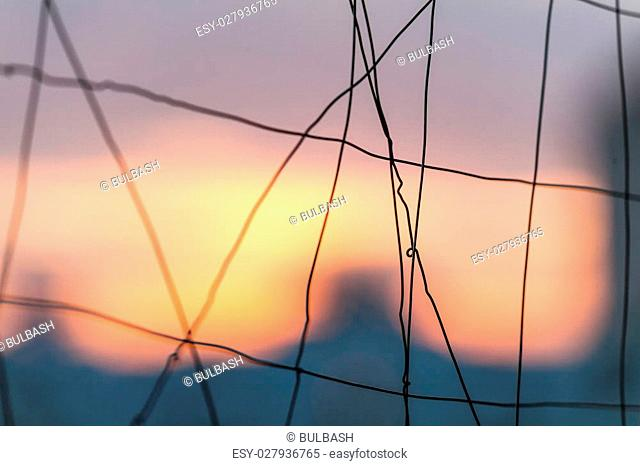 fence made of thin steel wire on blurred background
